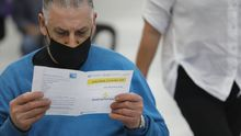 Un paciente lee el folleto informativo de la vacuna de AstraZeneca en el Ifevi de Vigo