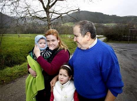 Álex y su hermana Iris posan con su madre y su abuelo en la aldea de Piquín.
