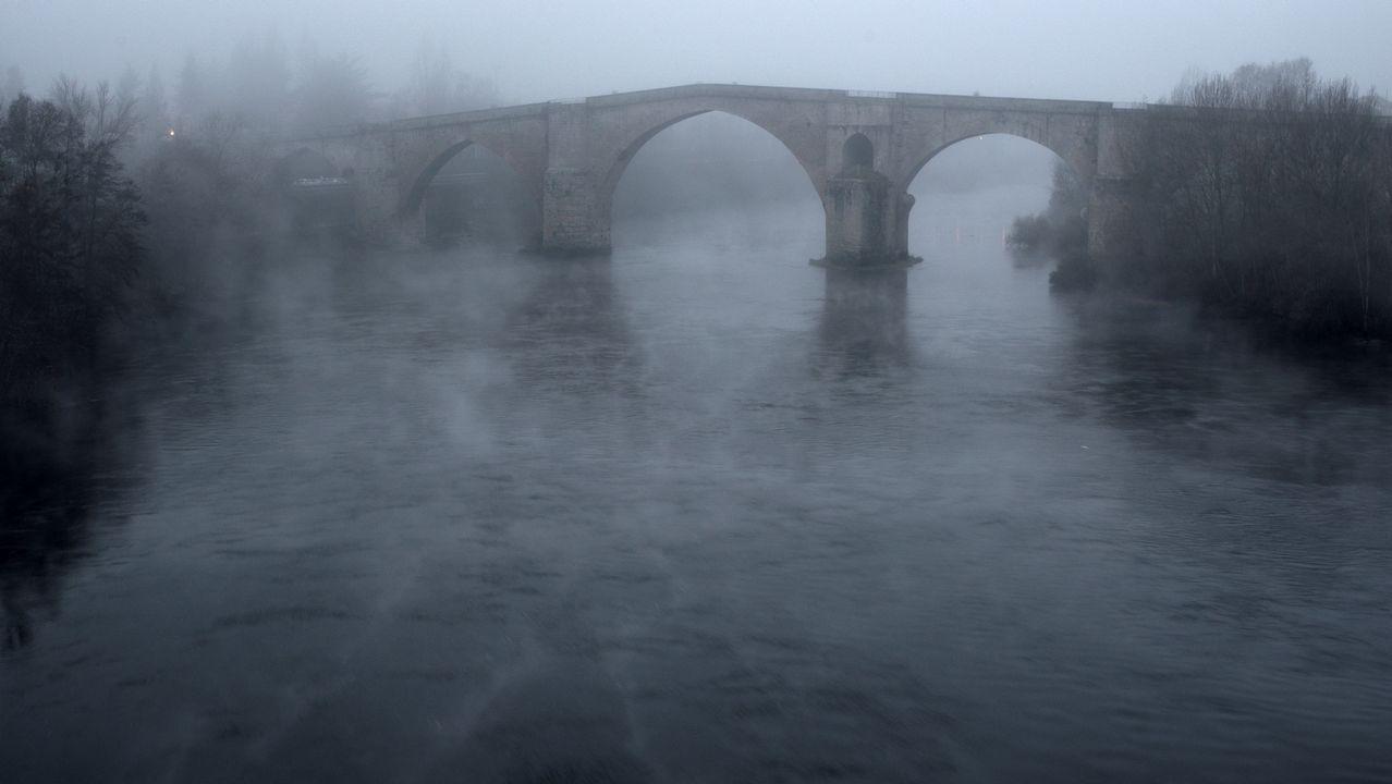 Galicia ha estado hoy bajo influencia anticiclónica, aunque un frente muy poco activo llegó por el tercio norte antes de que empiece el frío polar. En la imagen, vista de el río Miño y el Puente Romano de Ourense entre una densa niebla, a primera hora de esta mañana.