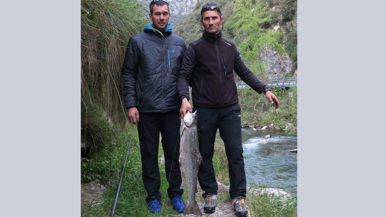 Dos pescadores sujeta el segundo salmón del Cares, pescado en  el coto Niserias