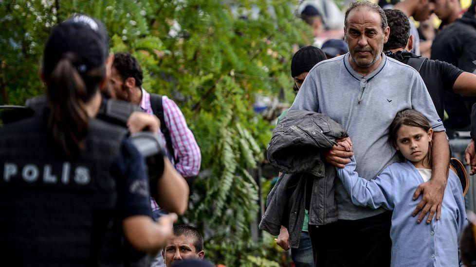 Un hombre y una niña esperan a que la policía turca los deje pasar para seguir una ruta hacia Europa que pasa por Estambul.