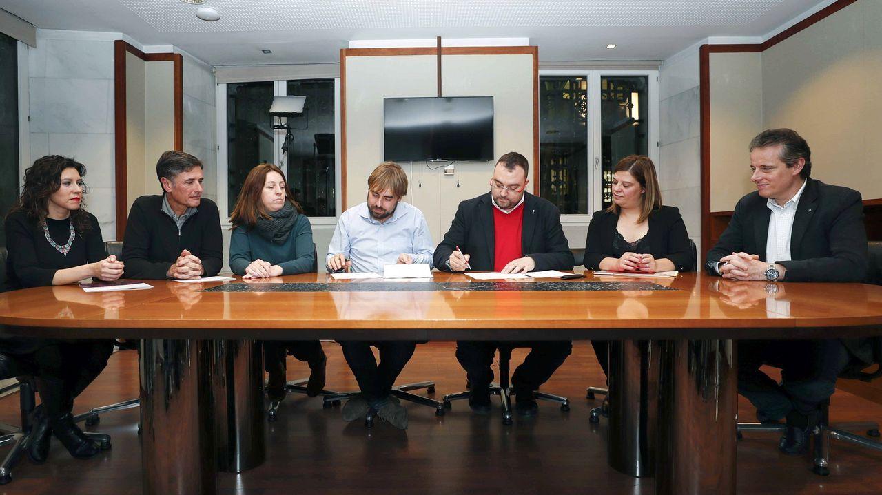 Los secretarios generales de los socialistas asturianos, Adrián Barbón (3d), y de Podemos Asturies, Daniel Ripa (4i), junto a responsables de los dos partidos, durante la firma de un acuerdo presupuestario para 2019.