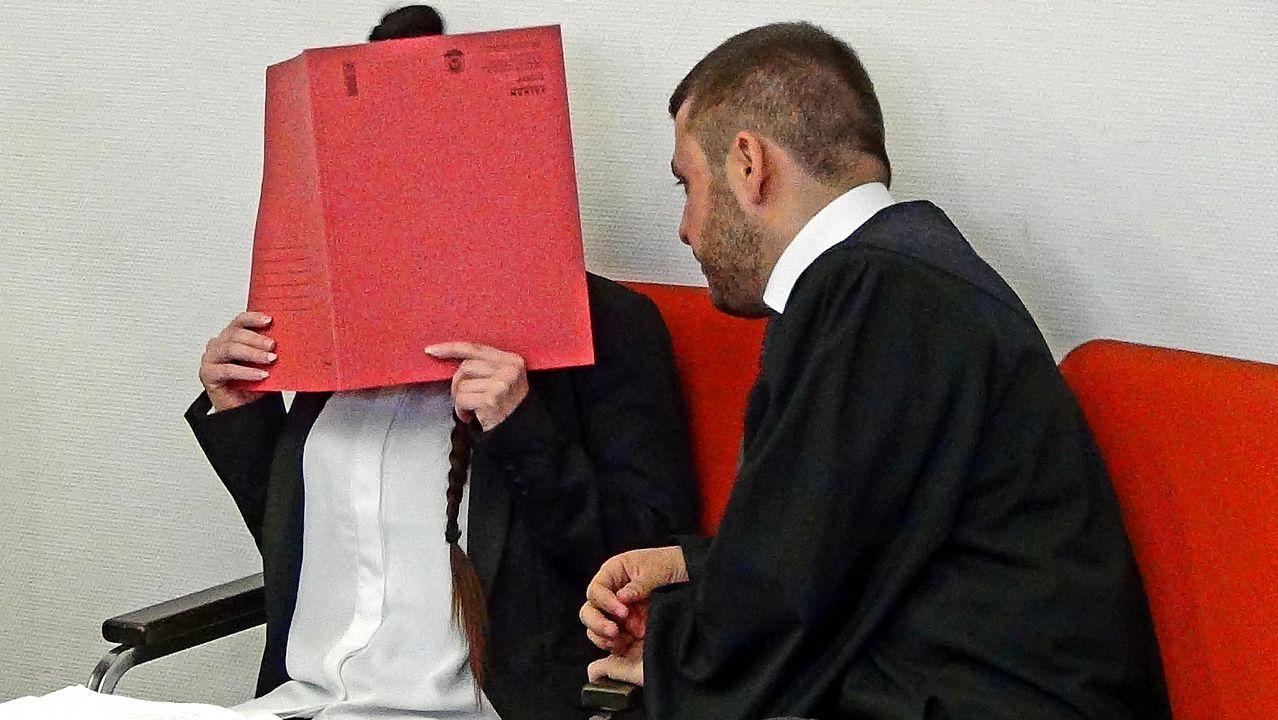 La acusada, con la cara cubierta, junto a su abogado