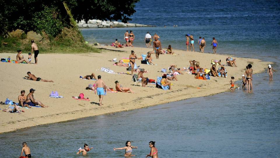 Gente bañándose en la playa de Caranza, donde se ha prohibido el baño