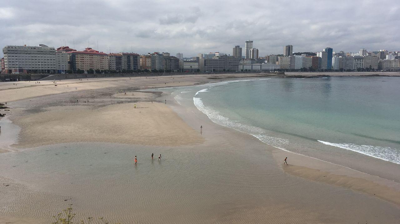 Miércoles lluvioso en Vigo.La intensa marea viva de estos días permite que Orzán y Riazor sean una sola playa durante la bajamar.