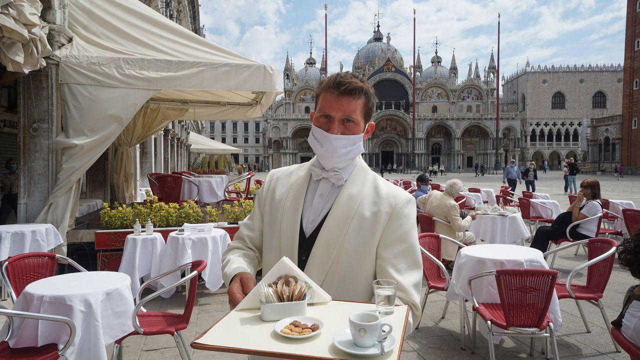 Un camareo del café Quadri de Venecia atiende con mascarilla a los clientes