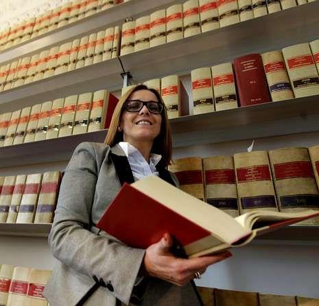 Cristina Bugarín delante de los anaqueles donde se hallan la enciclopedia de Aranzadi.
