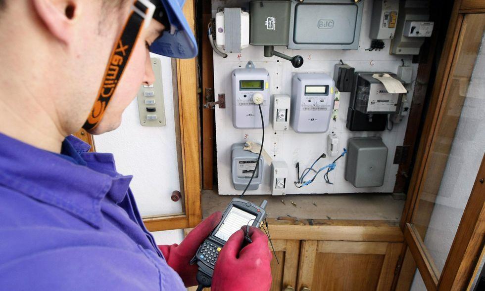 Un operario cambia el contador electromecánico a uno digital en un edificio.