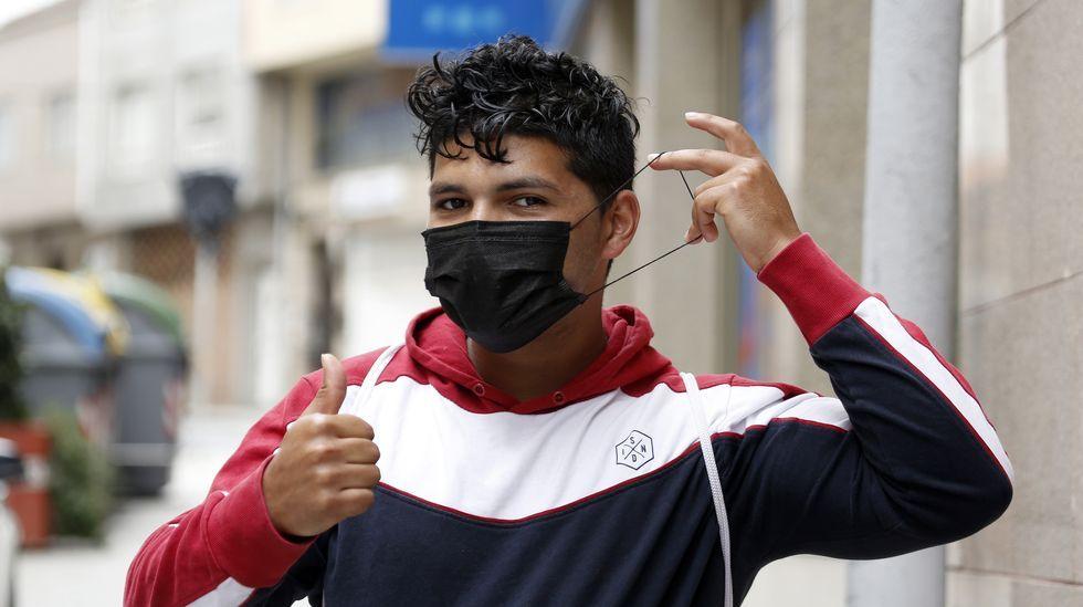 Un hombre camina con su mascarilla mientras habla por teléfono en una céntrica calle de Gijón