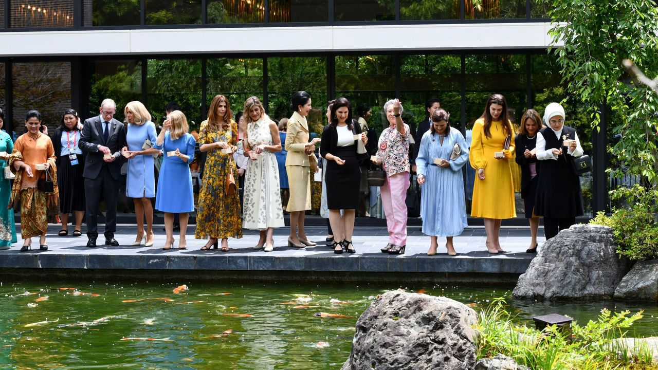 El marido de Teresa May y las esposas de los líderes reunidos en el G20 en Osaka, dan de comer a unos peces en el templo Tofuku-ji en Kioto, el pasado día 28