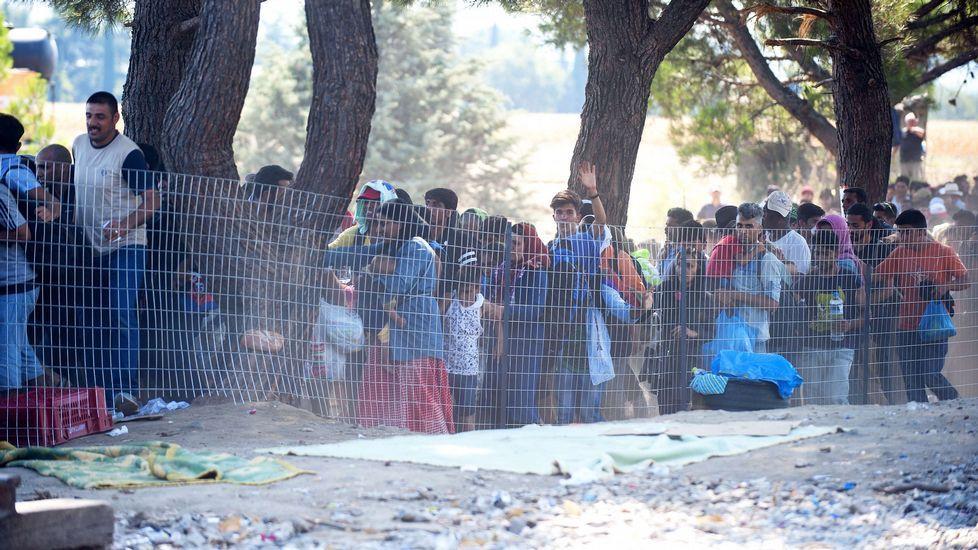 Inmigrantes esperan para cruzar la frontera entre Grecia y Macedonia para coger un tren hacia Serbia