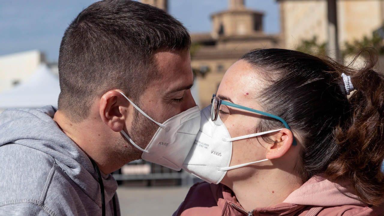 Una pareja se besa con mascarillas, en las que podría aplicarse el nanomaterial para eliminar el virus