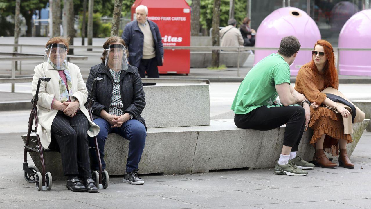 La Comunidad de Madrid se queda a medias en la fase 0,5.Un grupo de compostelanos descansan en un banco del centro de la ciudad