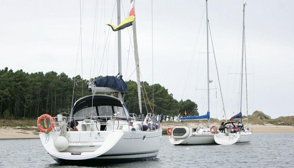 Embarcaciones participantes en la travesía durante la parada en una de las playas de A Illa.