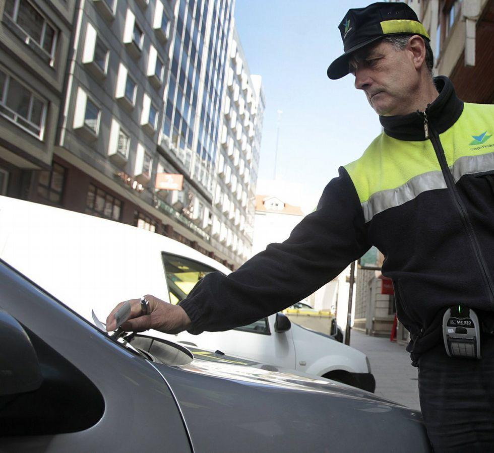 Un operario de la ORA multando ayer a un coche.