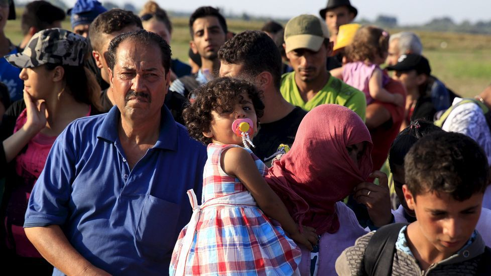 Inmigrantes sirios esperan el bus para ir a un campamento en Hungría, tras haber cruzado la frontera con Serbia