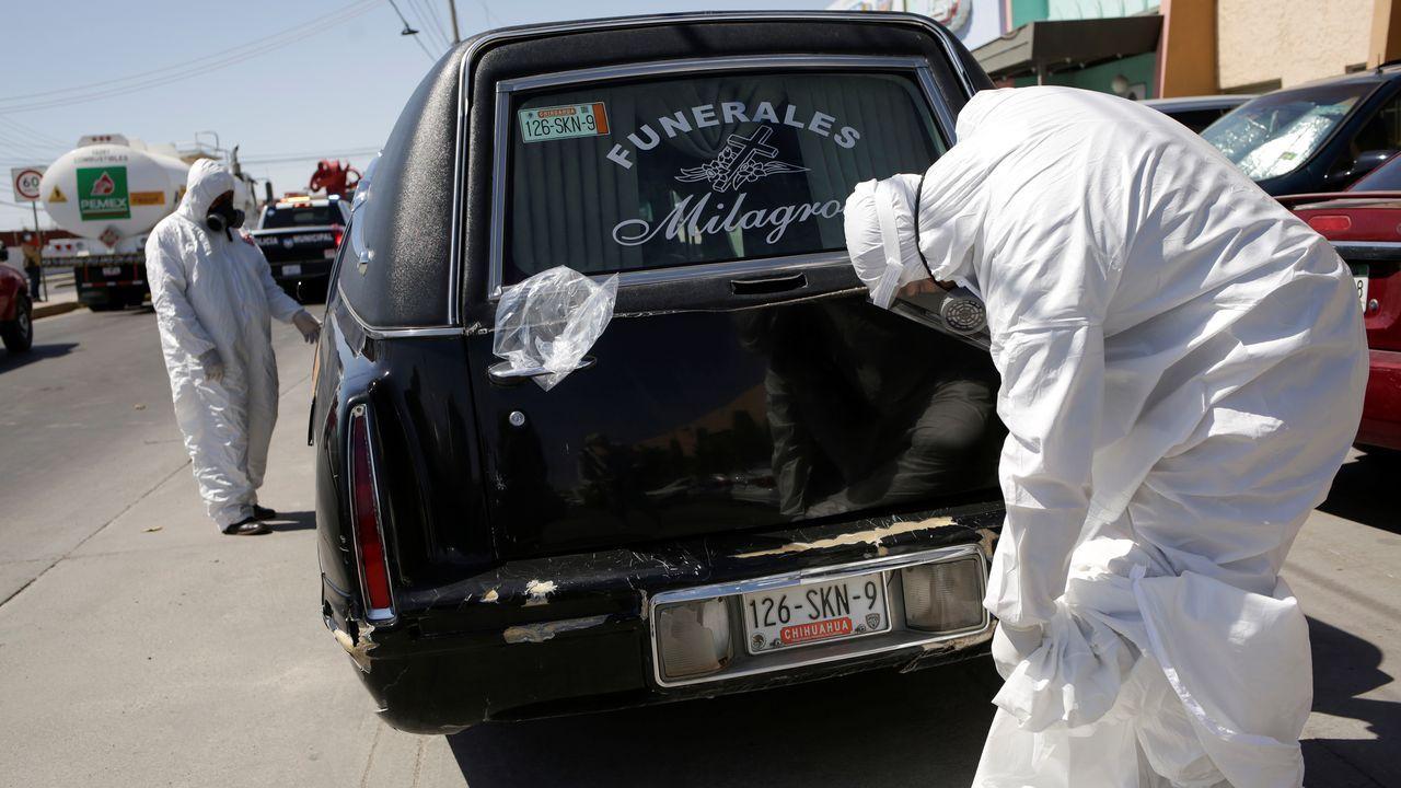 Trabajadores de una funeraria de Ciudad Juárez, en México, con los trajes de protección