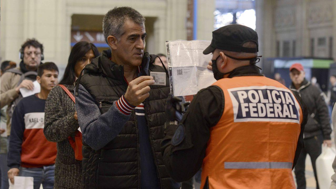 Un policía federal argentino comprueba las credenciales de un ciudadano que accede al tren durante la cuarentena