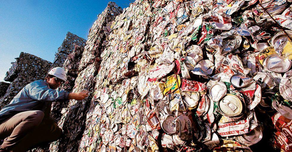 Un operario ante latas de bebidas comprimidas para su reciclaje en una fábrica norteamericana.