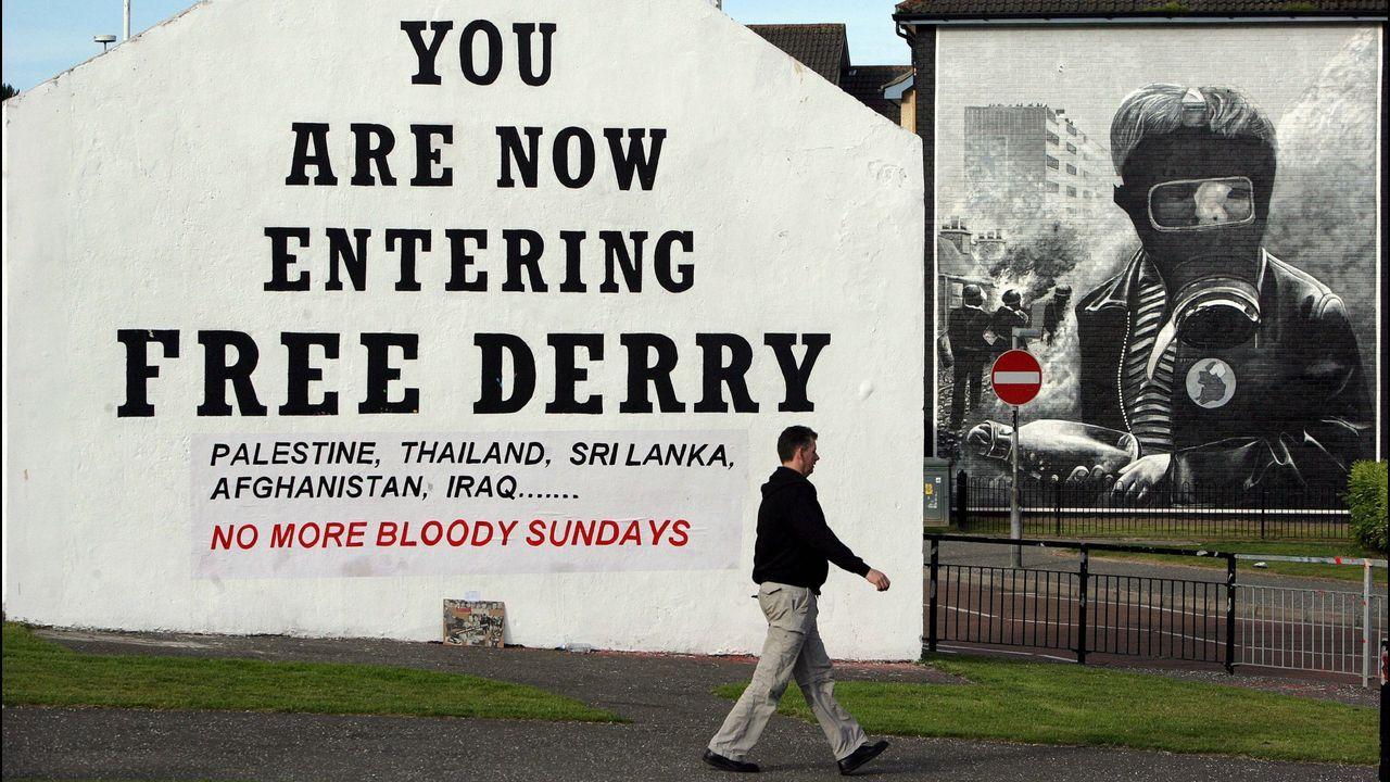 Un hombre pasa frente a uno de los murales de la zona católica de Derry