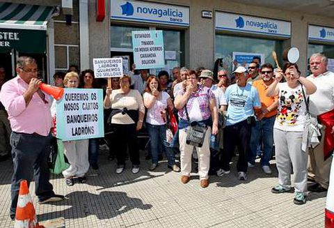 Afectados por las participaciones preferentes protestan delante de una sucursal de NCG Banco.