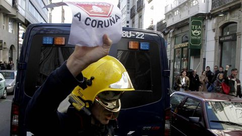 El bombero, con el cartel de Stop Desahucios en la mano.