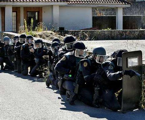 <span lang= es-es >Tensa espera para ocupar una casa</span>. Antes de acceder, los guardias toman posiciones. El primero de los agentes porta un escudo balístico para defenderse.