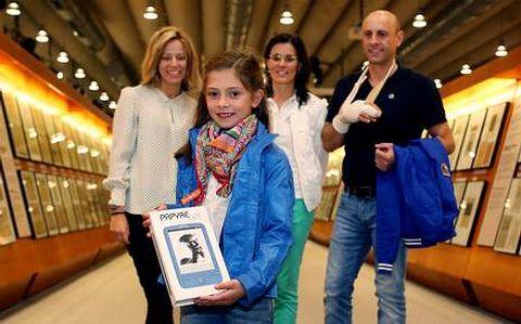 Candela Bedoya, acompañada por sus padres, recibió su «e-book» de manos de María García de Dios (izquierda).