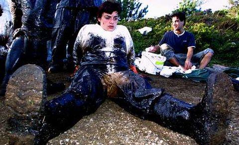 Un voluntario descansa tras retirar fuel en la costa de O Grove en diciembre del 2002.