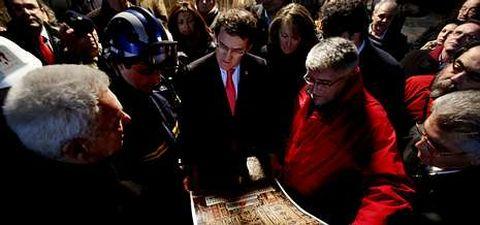 El presidente de la Xunta observa una reproducción del retablo barroco, flanqueado por el alcalde, el cura y el jefe de Protección Civil.