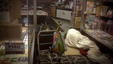 Un hombre durmiendo en el exterior de una librería en la ronda de Outeiro.