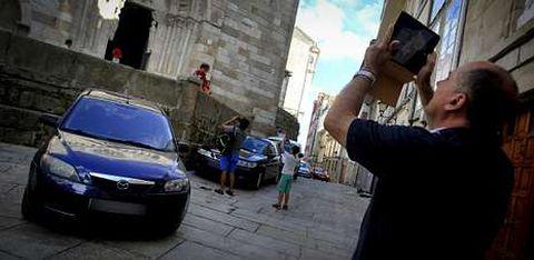 Turistas fotografiando ayer la iglesia de Santiago, con coches aparcados por todo su perímetro.