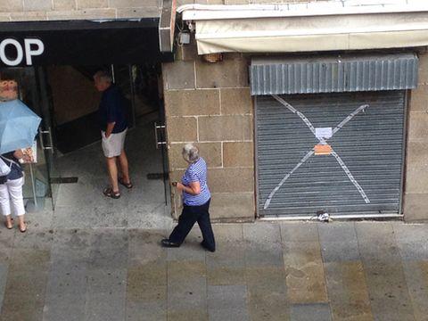 Unos turistas pasean entre los comercios precintados en la redada del miércoles