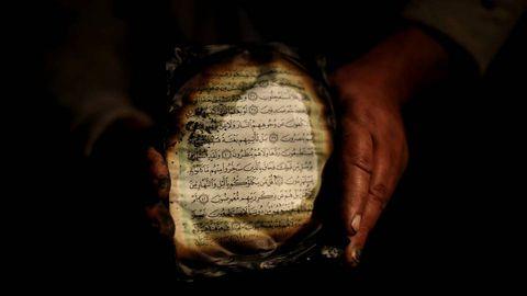 Un palestino muestra lo que queda de una copia del Corán mientras inspecciona los daños registrados en una mezquita de Cisjordania.