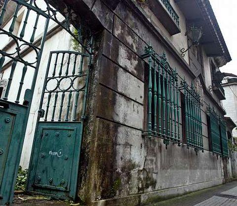 El edificio está a la entrada de la calle, al lado de la iglesia parroquial y pegado a otras casas.