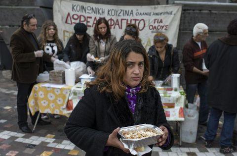 Una mujer en un puesto de reparto de comida, a cargo de una oenegé, en Atenas.