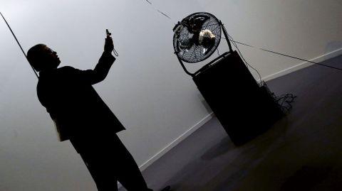 Un hombre fotografía una de las obras de la galería Riegner, de Colombia.