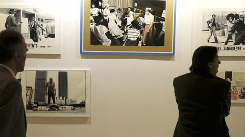 Dos hombres observan varias de las obras de la galería colombiana Doble Cero-Cero.