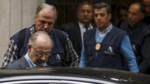 Rodrigo Rato entra en un coche de policía tras abandonar su domicilio