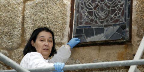 María Vázquez muestra el deterioro de la parte inferior de un vitral y detallle de la restauración.