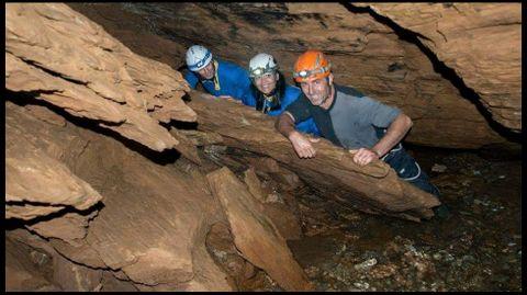 Tres miembros del grupo de excursionistas en un rincón situado a orillas del lago subterráneo