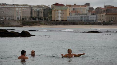 A pesar del temporal, gente bañándose en la playa de Riazor.