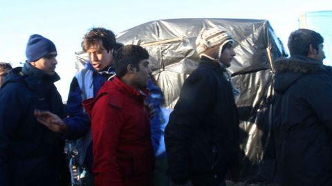 En la imagen Dan, un voluntario británico de Care 4 Calais, intenta poner orden en las largas filas que se apelotonan ante las furgonetas que llevan los alimentos.
