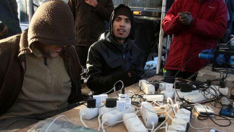 Refugiados reunidos alrededor de los cargadores de teléfonos móviles a su vez conectados a un trailer-generador en la zona sudanesa.
