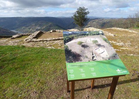 Un dos novos paneis situados xunto aos restos de estruturas construtivas desenterradas no castro