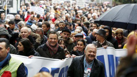 Xavier Vence, portavoz nacional del BNG, con bufanda de cuadros, sostiene una de las muchas pancartas reivindicativas que se desplegaron esta mañana en Santiago.