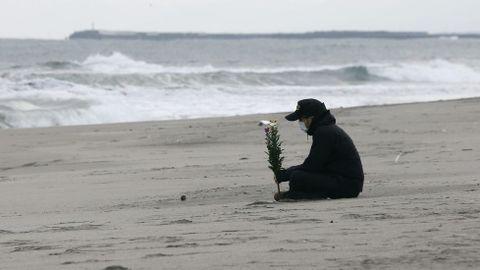Un hombre sostiene un ramo de flores ante el mar en memoria de las víctimas.