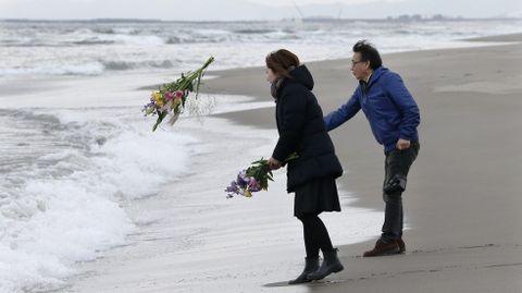 Mark Kanekita y Sadakuni Ito lanzan flores al mar en memoria de las víctimas.