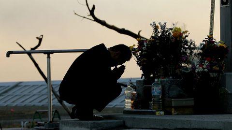 Un hombre reza ante un altar.