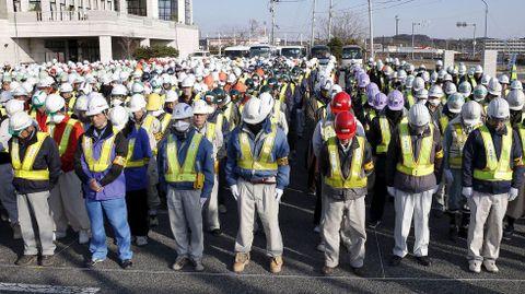 Operarios que trabajan en las labores de descontaminación de la zona, guardan un minuto de silencio.